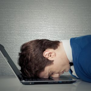 frustrated man laying head on laptop keyboard